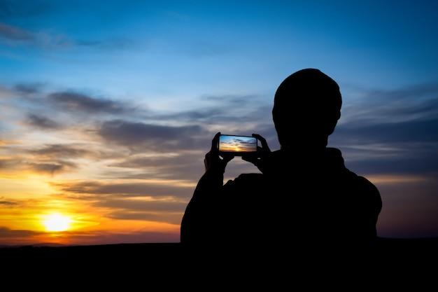 若い男のシルエットは、電話、スマートフォンで夕日を撮影します。旅行、ウォーキング。