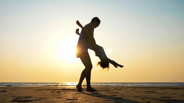 夕暮れ時のビーチで彼女の小さな娘を回転若い母親のシルエット