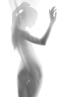 Силуэт молодой сексуальной женщины на белом фоне, откидываясь назад. студийный снимок