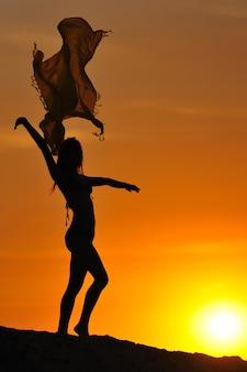 夏の日の日没時に立って、上げられた手でパレオを保持しているビキニの若いスリムな女性のシルエット。内面の美しさと自由の概念