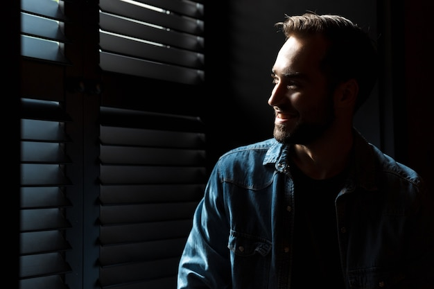 Силуэт молодого улыбающегося человека, стоящего в темной комнате на фоне солнечных лучей из окна на теневых жалюзи