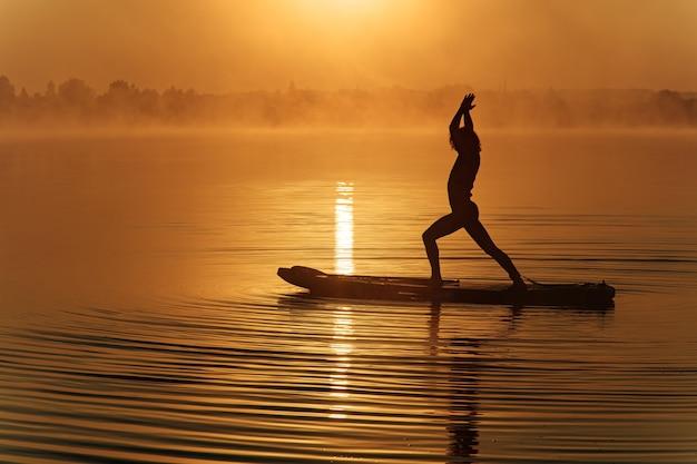 湖の夏の日の出の間にスタンドアップパドルボードでヨガをしている若いスポーツマンのシルエット。
