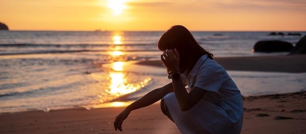 ビーチで美しい夕日に対する若い女性のシルエット