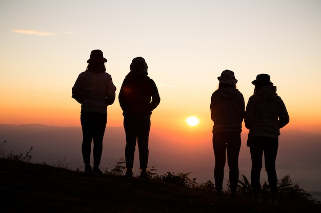 リラックスした山の上に若い女性のシルエットが立っています。