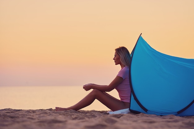 Силуэт молодой женщины перед палаткой на пляже на рассвете