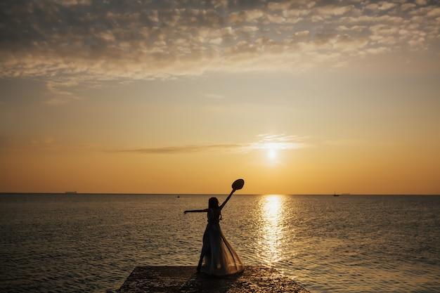 Силуэт молодой женщины в длинном платье, наблюдая морской закат.