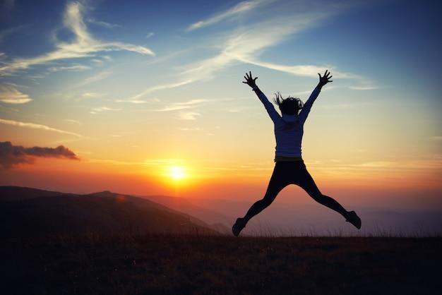 青い空と夕日に向かってジャンプする若い女性のシルエット。