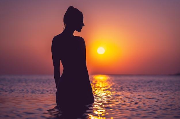 Силуэт молодой женщины, практикующей йогу на пляже на рассвете