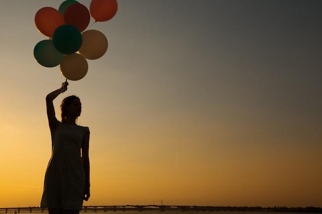 Силуэт молодой женщины с летающими воздушными шарами против неба. концепция счастья и мечты