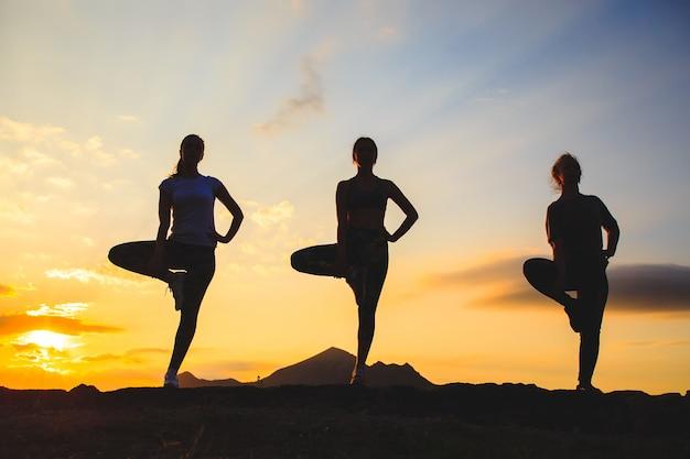 美しい山の場所で日没や日の出のヨガやピラティスを練習する若い女性のシルエット。