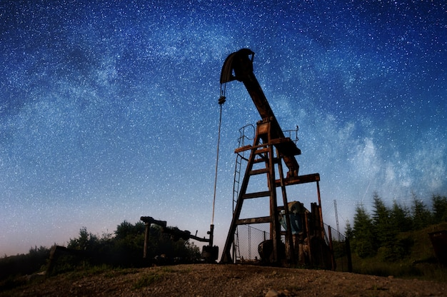 Silhouette of oil pump is pumping crude on the oil field in the night under sky with stars.