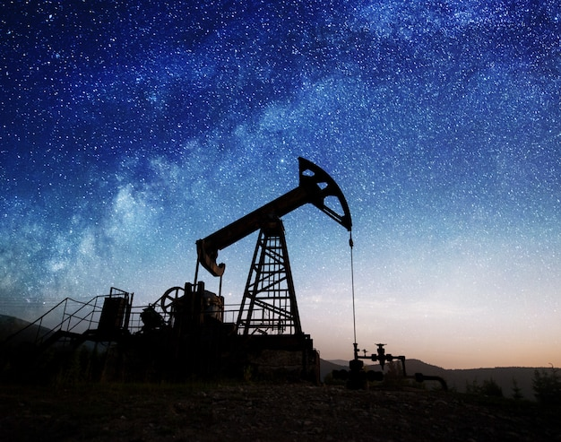 Silhouette of oil pump jack working in the night