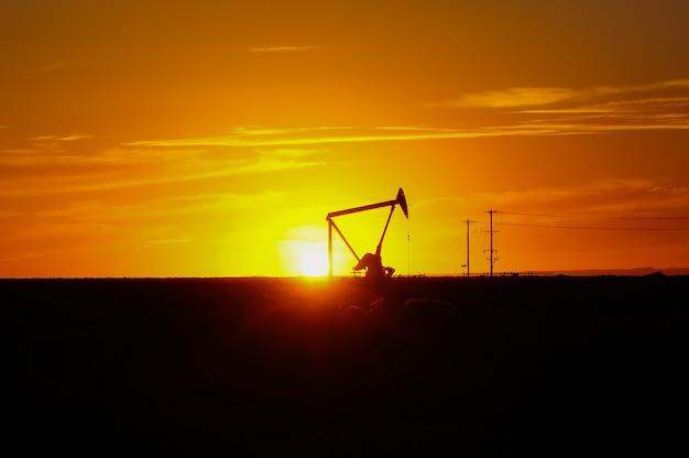夕焼け空を背景に油田でシルエットオイルポンプ