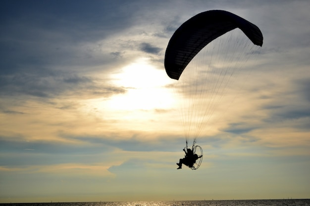 Silhouette one paramotor over sea and sunset sky
