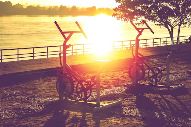 Silhouette of outdoor stationary bikes in the riverside park at sunrise.