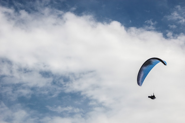 Silhouette of parachute on blue sky background