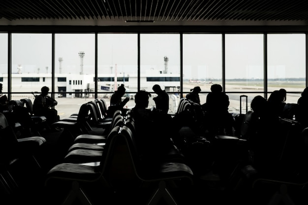 Silhouette of passangers waiting for the flight at the airport