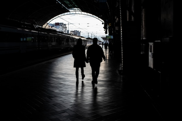 Silhouette of passengers in a train station.