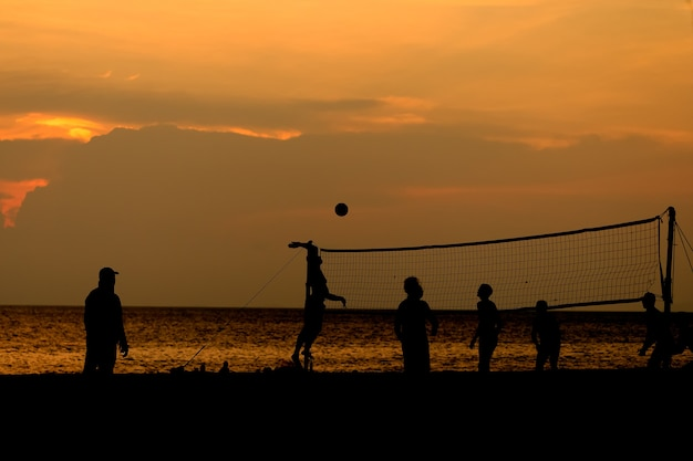 Silhouette people are playing beach volleyball.