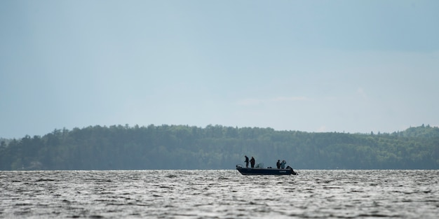Silhouette of people on boat in a lake, lake of the woods, ontario, canada