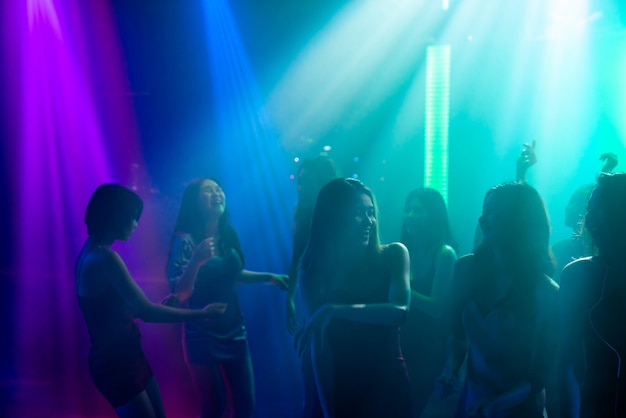 Silhouette of people dance in disco night club to music from dj on stage