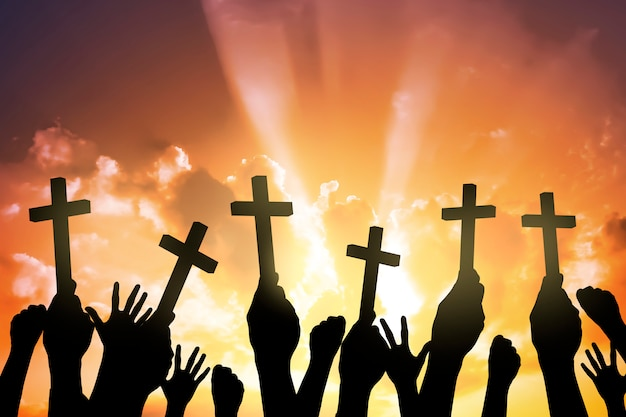 Silhouette of people holding christian cross