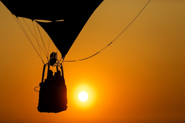 Silhouette of people in hot air balloon basket flying in sunset sky