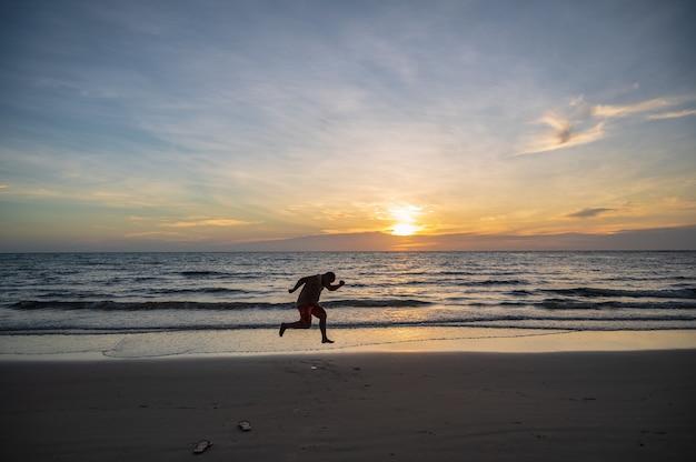 비수기 여행에서 코쿳 섬의 아름다운 목가적인 바다 경치와 함께 점프하는 실루엣 사람들. 코쿳이라고도 알려진 코쿳은 태국 만에 있는 섬입니다.