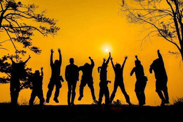 Силуэт люди друзей прыгают