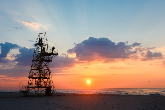 Silhouette of people on a rescue tower on a sandy beach at sunset.