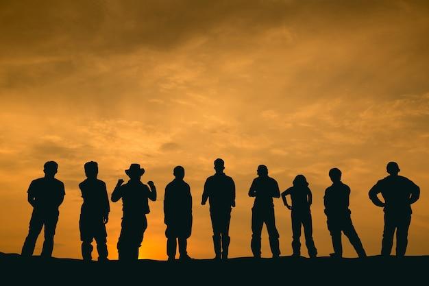 シルエットの人々のチームは、夕暮れ時に丘の上に立って前方を見ます。