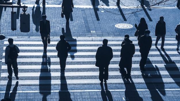 Silhouette people walk on pedestrian crosswalk at junction street