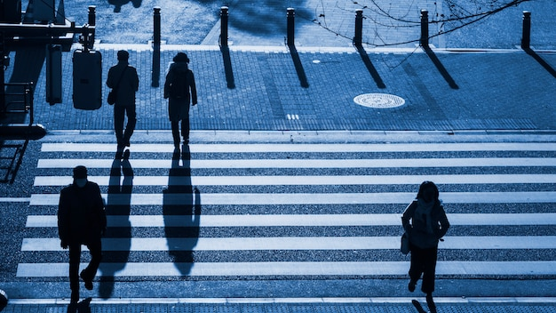 Silhouette people walk on pedestrian crosswalk