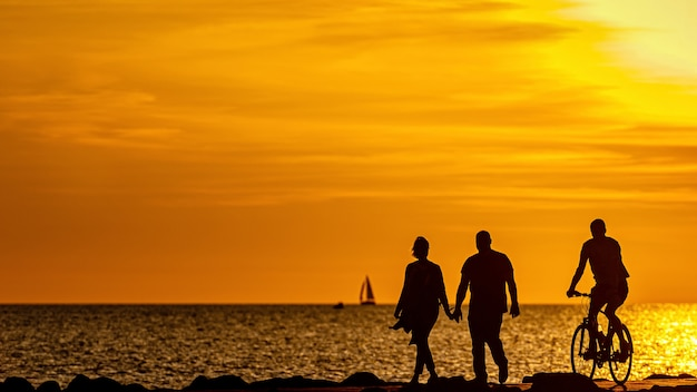 Silhouette of people walking and biking on the pier during the golden hour of sunrise