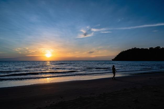 비수기 여행의 코쿠드 섬에서 아름다운 목가적인 바다 경치의 일몰을 감상할 수 있는 실루엣 사람들. 코 쿠트라고도 알려진 코 쿠드는 태국 만에 있는 섬입니다.
