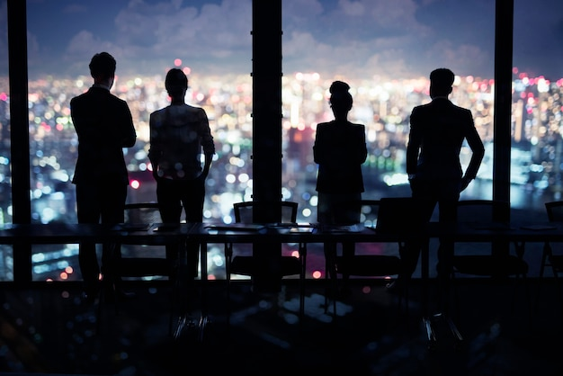 Silhouette of people working in the office at night
