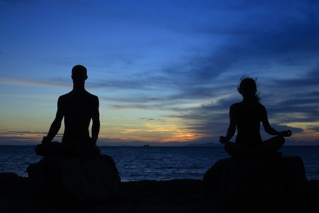 Silhouette of perfect body man and woman act yoga on the rock with sea sunet space