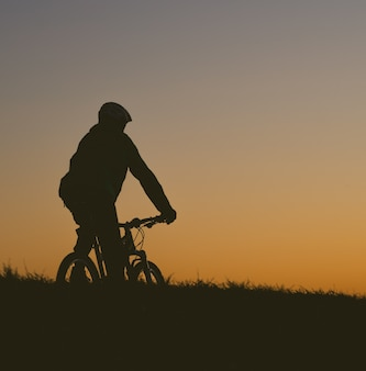 Silhouette of a person riding a bicycle on a field during a sunset