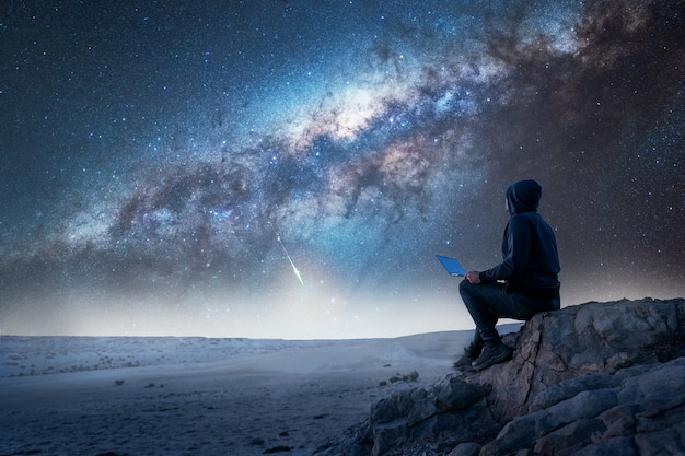 Silhouette of a person sitting on the top of the mountain with laptop staring the milky way