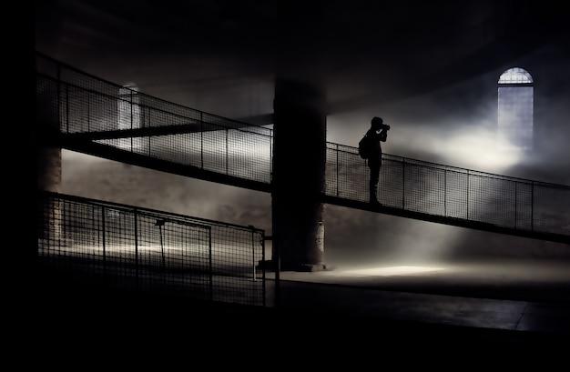 Siluetta della persona in piedi sul ponte mentre si scatta la foto