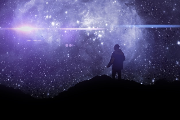 A silhouette of a person standing on top of mountain and watch the sky galaxy. elements of this image furnished by nasa