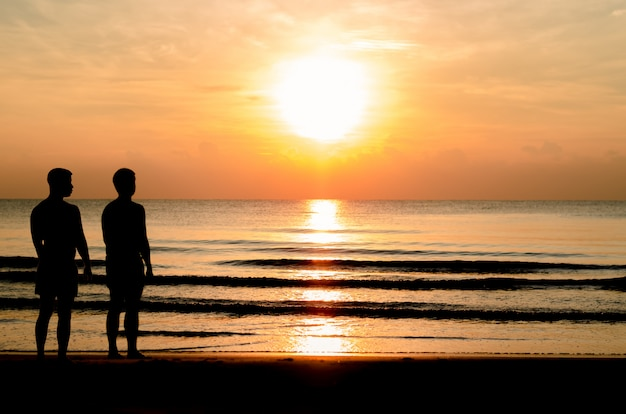 The silhouette photo of the gay couple standing together on the beach.