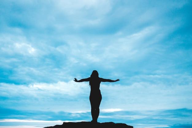 그녀의 손을 올리는 여자의 실루엣 사진