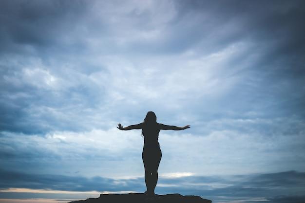 岩の上に立っている女性のシルエット写真