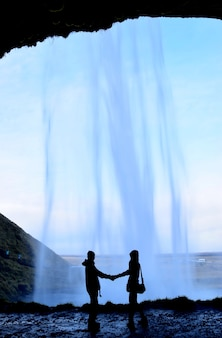 The silhouette picture of young couple in the cave behind the waterfall in iceland.