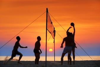 силуэт играть в пляжный волейбол. Время захода солнца