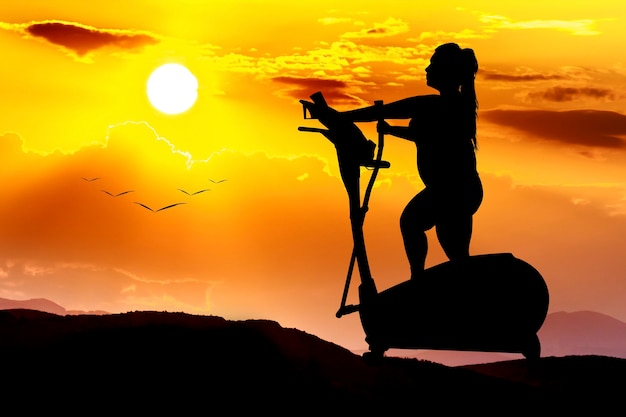 Silhouette of a plus-sized girl on an cardio exercise machine, a sunset image that motivates the concept of a way to a healthy lifestyle Premium Photo