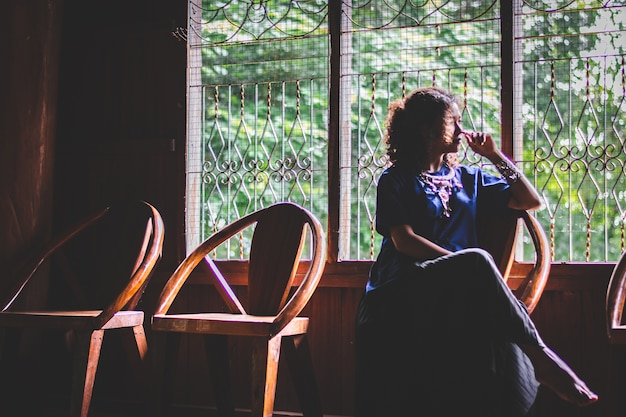 Silhouette of portrait  beautiful asian woman, depress, with local dress sitting beside the window a