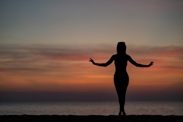 Silhouette portrait of woman wearing bikini on the beach, golden sunset moment. holiday and travelling concept.