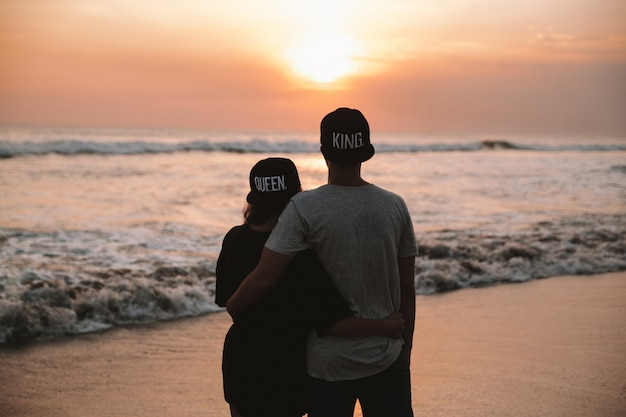Silhouette portrait of young romantic couple walking on the beach. girl and her boyfriend posing at golden colorful sunset. they hugging and dreaming